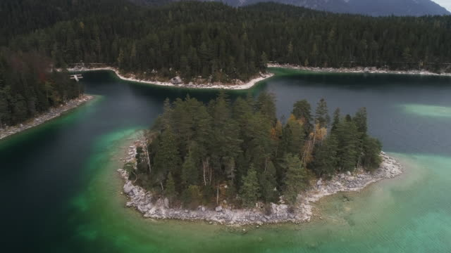 vídeos de stock, filmes e b-roll de panning drone shot of an island covered in trees in lake eibsee, germany - montanha zugspitze
