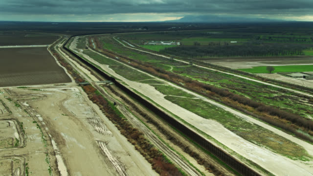 panning drone shot of farmland on both sides of u.s.-mexico border wall - international border barrier stock videos & royalty-free footage
