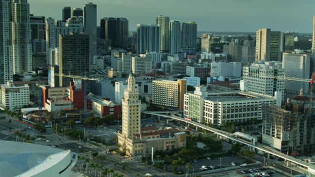 panning drone shot of freedom tower and downtown miami at sunrise - miami stock-videos und b-roll-filmmaterial
