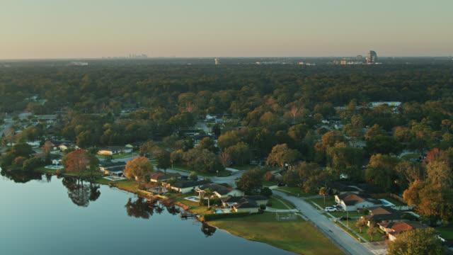 panning drone shot of homes on the shore of rock lake in longwood, florida - lakeshore stock videos & royalty-free footage