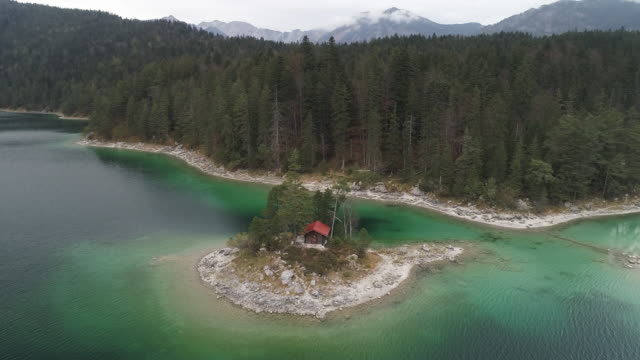 vídeos de stock, filmes e b-roll de panning drone shot showing a log cabin on an island in lake eibsee, germany - montanhas wetterstein