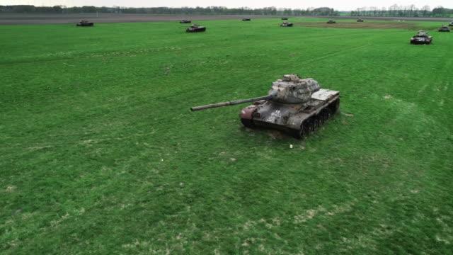 panning drone shot showing abandoned tanks in a field, germany - gruppe von gegenständen stock-videos und b-roll-filmmaterial