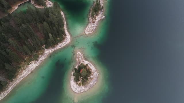 panning drone shot showing an island in lake eibsee, germany - 囲む点の映像素材/bロール