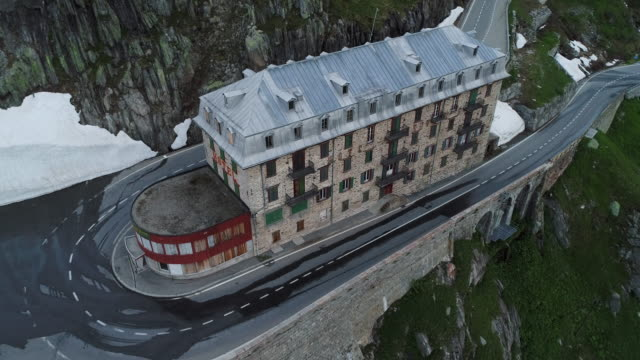 panning drone shot showing the abandoned belvédère hotel, switzerland - winding road stock videos & royalty-free footage