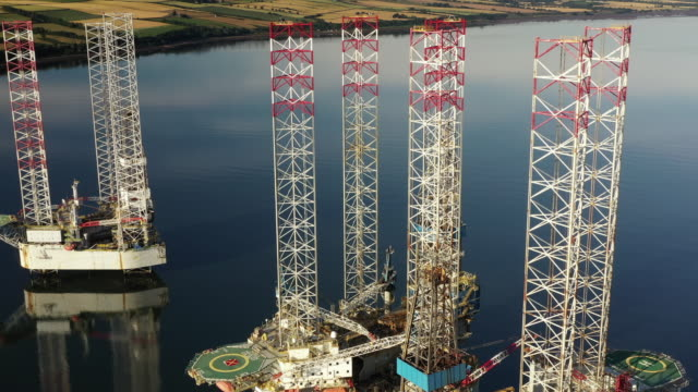 panning drone shot showing three abandoned oil rigs off the coastline, cromarty firth, scotland, united kingdom - pipeline stock videos & royalty-free footage