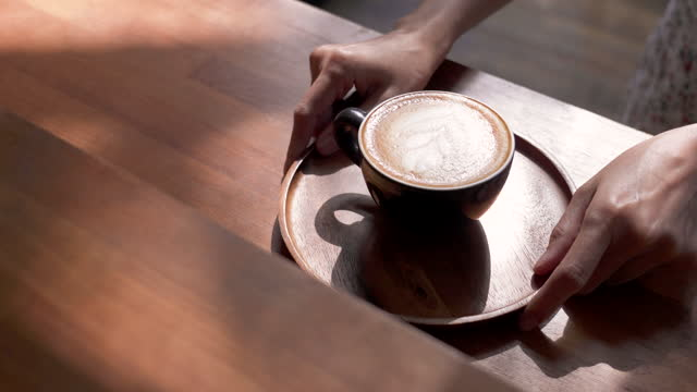 panning female hans serving hot coffee cup on table with morning sunshine. - mug stock videos & royalty-free footage