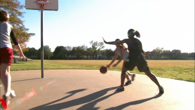 vídeos de stock, filmes e b-roll de panning four young women playing basketball - passe de bola