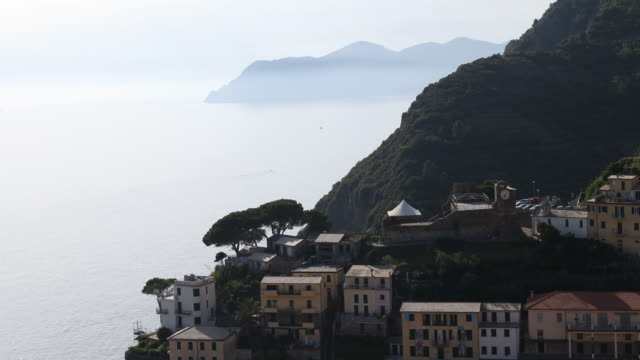 Panning from bottom to top of a picturesque village of the Cinque Terre on the Italian Riveria Liguria Italy with the Mediterranean Sea and a rock in...
