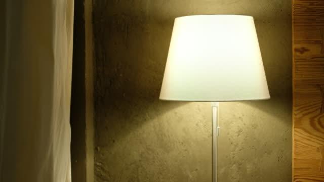 vídeos de stock e filmes b-roll de panning from curtain to bed table lamp in bedroom - lâmpada elétrica