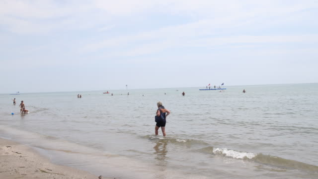 panning from left to right on the beach and adriatic sea in caorle, veneto, italy - a woman walks along the beach through the water while kids play... - adriatic sea stock videos & royalty-free footage