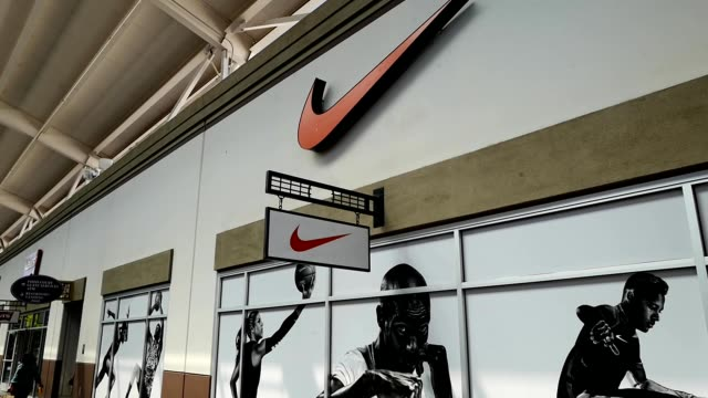 panning from logo for nike on facade of store to display on wall 2019 - nike designer label stock videos and b-roll footage
