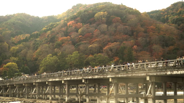 panning from low angle view: Togetsukyo Bridge in Kyoto, Japan amid Autumn in weekend