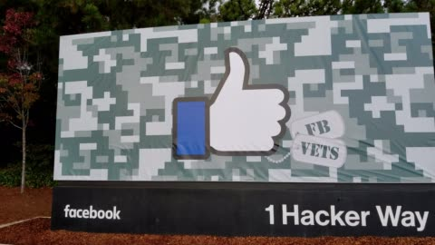 panning from main sign to a group of visitors walking through the woods towards the entrance to headquarters of social media company facebook, in the... - headquarters stock videos & royalty-free footage