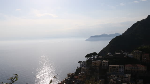 Panning from right to left of a picturesque village of the Cinque Terre to the Mediterranean Sea and rocks in the background on the Italian Riveria...