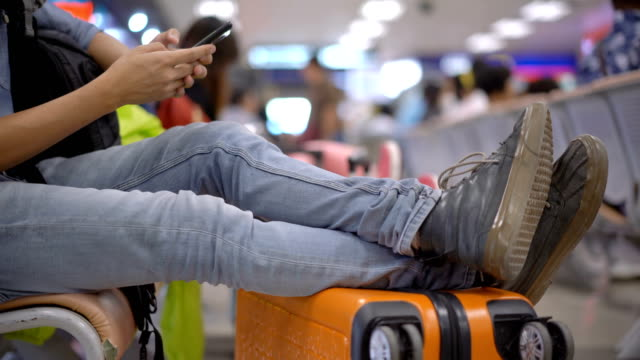 panning from shoe to face of asian man who using smartphone when he waiting flight in airport - waiting stock videos & royalty-free footage