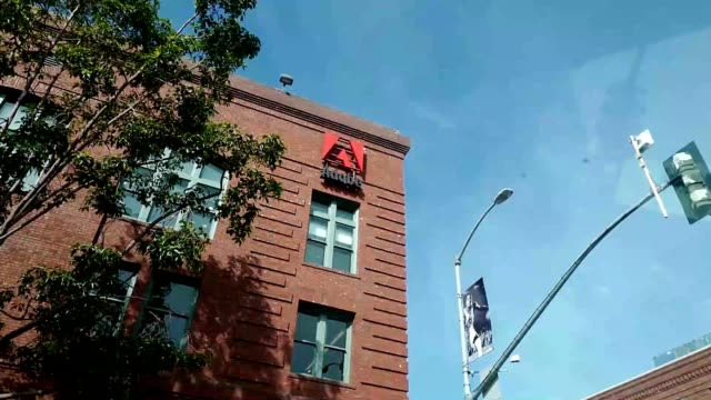 panning from sign with logo on facade at office of computer software company adobe in the south of market neighborhood of san francisco, california... - logo stock videos & royalty-free footage