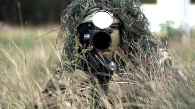 vídeos de stock, filmes e b-roll de panorâmica vista frontal: o rosto do atirador totalmente equipado e pano-camuflado esperando entre grama - rifle