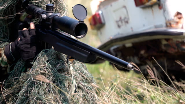 panning: fully equipped and cloth-camouflaged sniper waiting among grass
