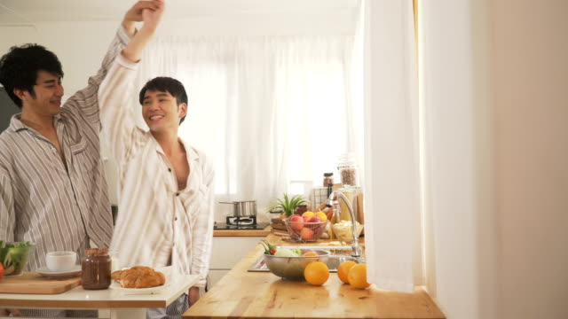 panning: gay couple dancing in the modern kitchen after they wake up in morning