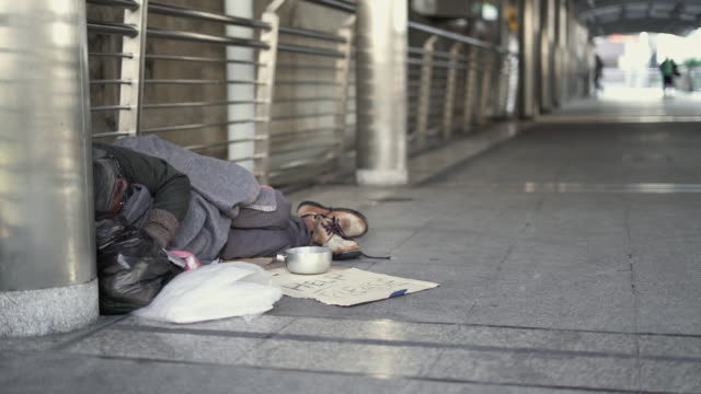 panning: homeless sleeping on the footpath. - povertà video stock e b–roll