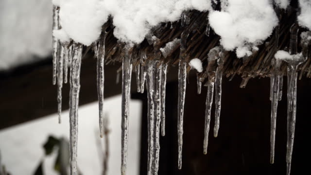 panning: It is cold until water form frozen spear on house roof at Shirakawago village