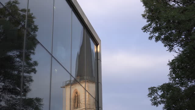 panning large windows on the side of a modern building reflecting a nearby old church steeple, with bright blue sky and a lush green tree - erfurt, germany - new stock videos & royalty-free footage