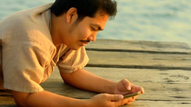 vídeos de stock, filmes e b-roll de panning: colocar homem writting uma mensagem com smartphone - mensagem