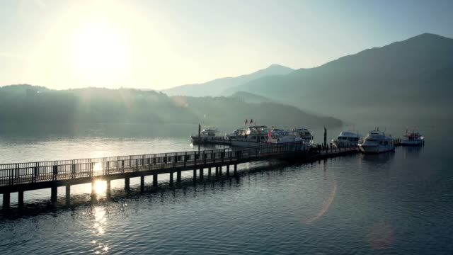 panning left to chaowu pier with sunlight reflection on the lake, sun moon lake, taiwan - sun moon lake stock videos and b-roll footage