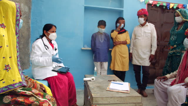 panning left to doctor and her medical staff make hand gestures and signs briefing a traditional indian family as they stand and listen carefully wearing their masks - examining stock videos & royalty-free footage