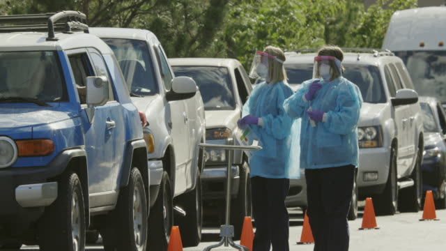 vídeos de stock e filmes b-roll de panning long shot of two female nurses wearing gowns, surgical face masks, gloves, and face shield talking to patients in their cars in a drive-up (drive through) covid-19 (coronavirus) testing line outside a medical clinic/hospital outdoors (second wave) - amostra médica