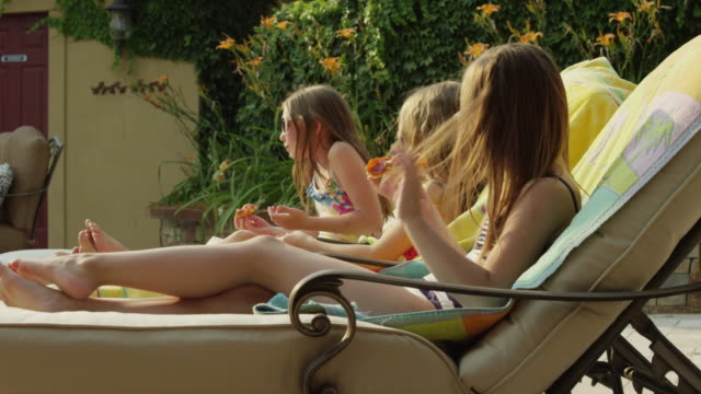 panning medium shot of girls in bathing suits eating pizza at poolside / cedar hills, utah, united states - poolside stock videos and b-roll footage