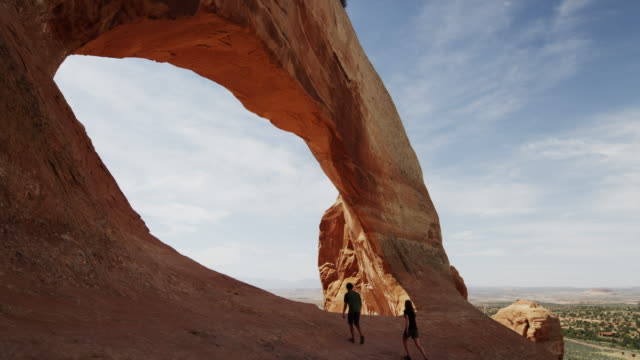 panning, medium shot of people hiking at wilson arch / wilson arch, utah, united states,  - natural arch stock videos & royalty-free footage