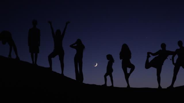 stockvideo's en b-roll-footage met panning medium shot of people silhouetted on hill against night sky / lake powell, utah, united states - powellmeer