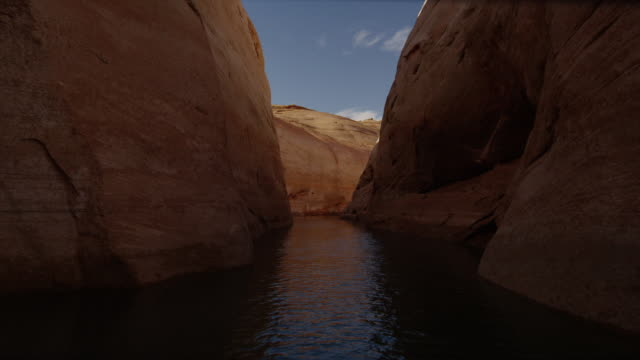 panning medium shot of rock formation bordering lake / lake powell, utah, united states - lake powell stock videos & royalty-free footage