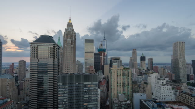 Panning motion controlled time lapse unique view from downtown Manhattan. Looking towards World Trade Center, Midtown NYC, Empire State Building. Storm clouds rolling in during sunset, blue hour, early night.