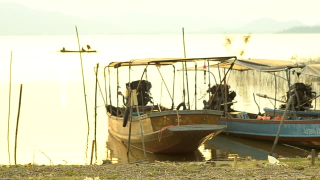 panning : motorboat in lake at twilight - longtail boat stock videos & royalty-free footage