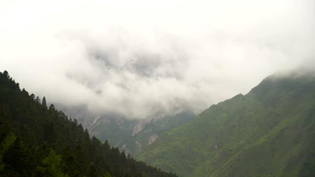 panning: mountain range under dense cloud at huanglong valley landscape, sichuan, china - mountain range stock videos & royalty-free footage