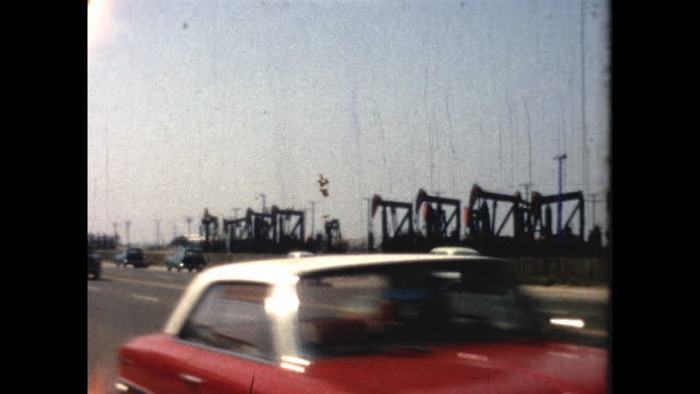 panning of highway busy with cars; oil drilling machines in the background - american culture stock videos & royalty-free footage