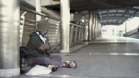 vidéos et rushes de panoramique des sans-abri hommes âgés assis sur le trottoir. - fragilité