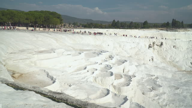 panning on traveler crowds walking on range of pamukkale pools without flowing water, droughts, in summer.  layers of travertines form terraces of carbonate minerals in pamukkale, natural landmark of natural phenomenon, on sunset at southwest turkey. - natural landmark stock videos & royalty-free footage