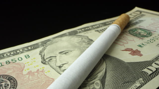 panning over cigarette on top of ten dollar bill - smoking issues stock videos & royalty-free footage