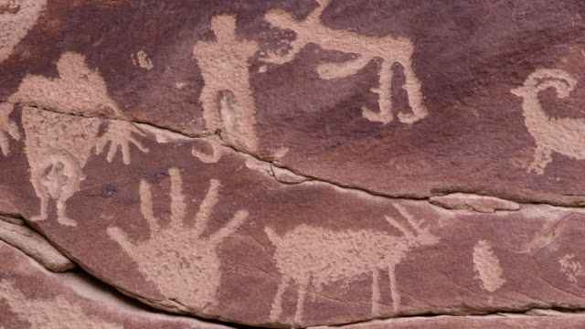 vídeos de stock, filmes e b-roll de panning over petroglyph carving of people and hands - anasazi