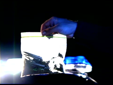 panning over policeman holding bag of marijuana - narcotic stock videos & royalty-free footage