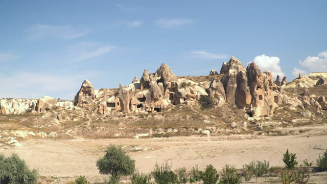 panning panoramic view of the valley as an eroded resident building in a mountain range in goreme village, turkey on a clear sky and sunny day. rural cappadocia landscape. volcanic mountains in goreme national park. countryside for a travel destination. - middle east stock videos & royalty-free footage