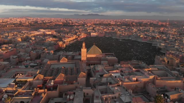 Panning parallax drone shot of a Moroccan city at sunset