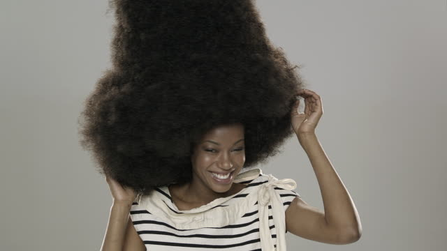 panning portrait of beautiful young woman with large afro dancing