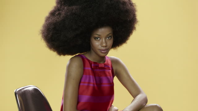 panning portrait of beautiful young woman with large afro