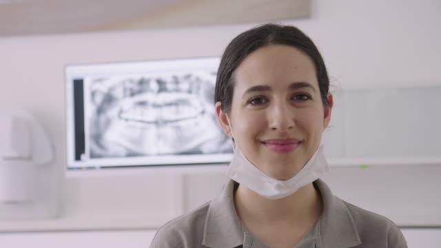 panning-porträt einer selbstbewussten zahnarzthelferin - looking at camera stock-videos und b-roll-filmmaterial