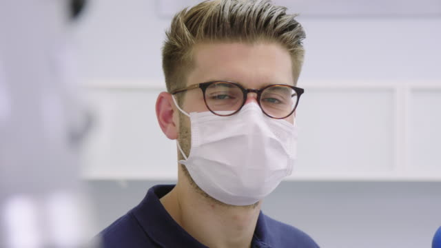 panning portrait of confident dentist at hospital - protective workwear stock videos & royalty-free footage
