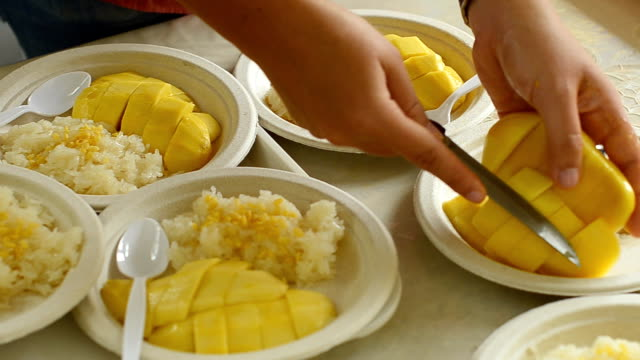 panning : put slice mango into sticky rice - paper plate stock videos & royalty-free footage